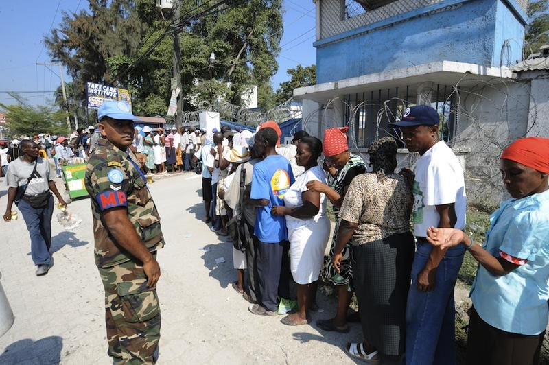UN police patrol as people wait in line in Port au Prince.