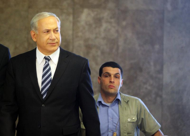 Israeli Prime Minister Benjamin Netanyahu looks to the press and government workers at the top of the stairs as he arrives to his Jerusalem offices to chair the weekly cabinet meeting on March 14.
