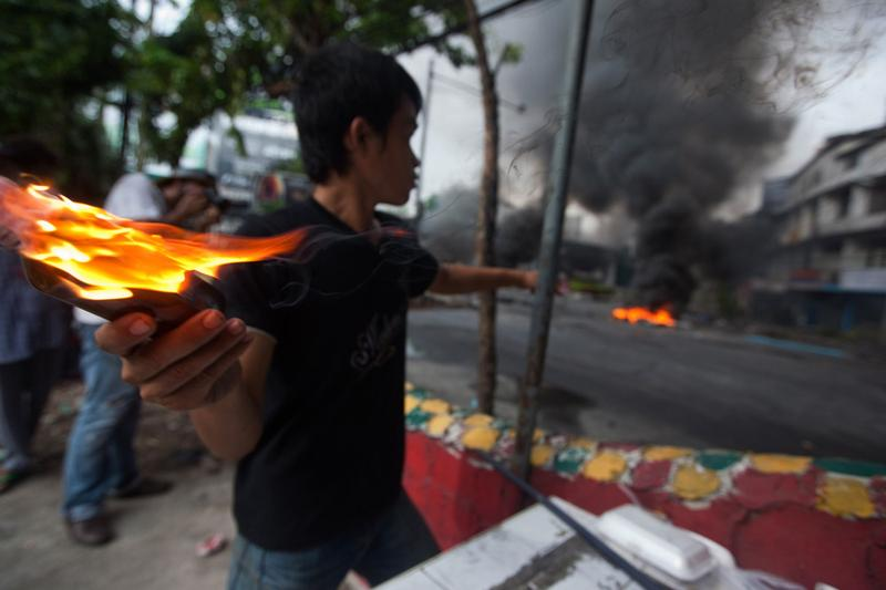 An anti-government protester 'Red Shirt' throws a molotov cocktail toward Thai security forces as the violence in central Bangkok continues on May 16, 2010 in Bangkok, Thailand.