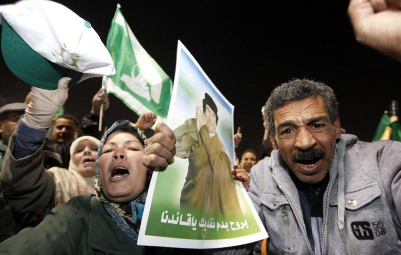 Supporters of Libyan leader Moammar Gadhafi shout slogans while holding his picture during a pro-government rally in Tripoli on February 18, 2011.