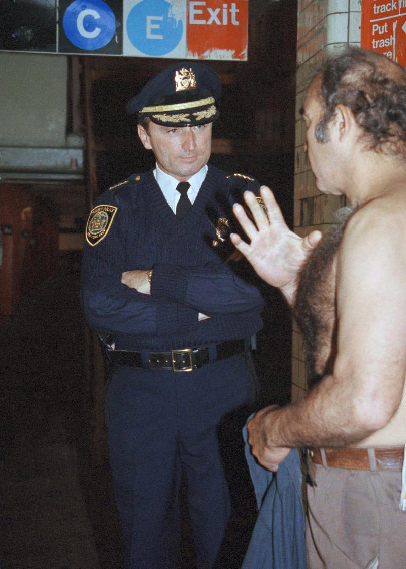 Bill Bratton, chief of the New York Transit Police, talks to a homeless man in New York, Nov. 21, 1991, on a routine tour of the New York City subway system.