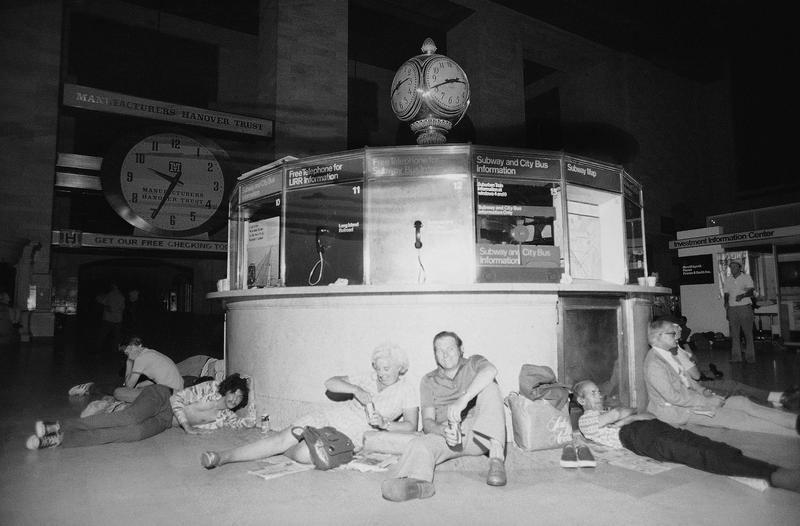 People huddle against the information kiosk in New York's Grand Central Station, July 14, 1977 after being stranded by a power failure in the city, its boroughs and some neighboring areas.