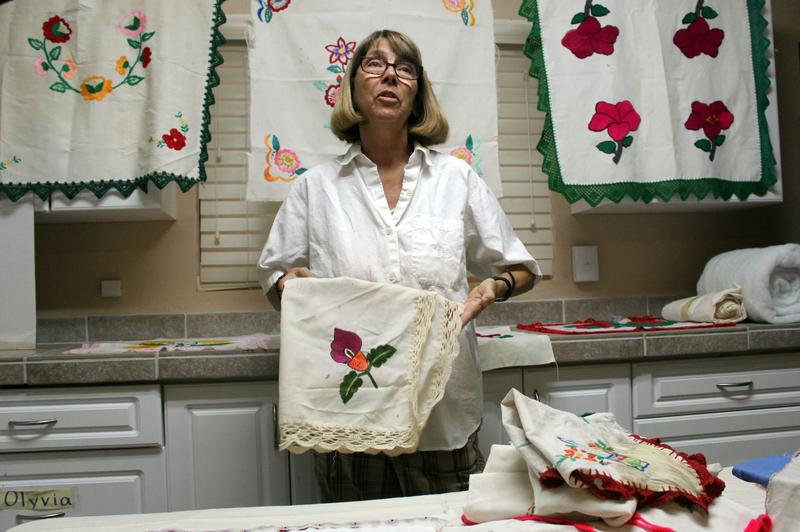 Artist Valerie James surrounded by freshly laundered linens found near the border crossing in the Senora desert.