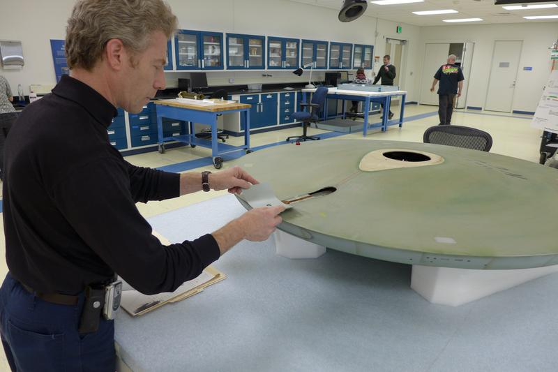 Museum Specialist David Wilson finds the exact color match to the grey paint inside the saucer