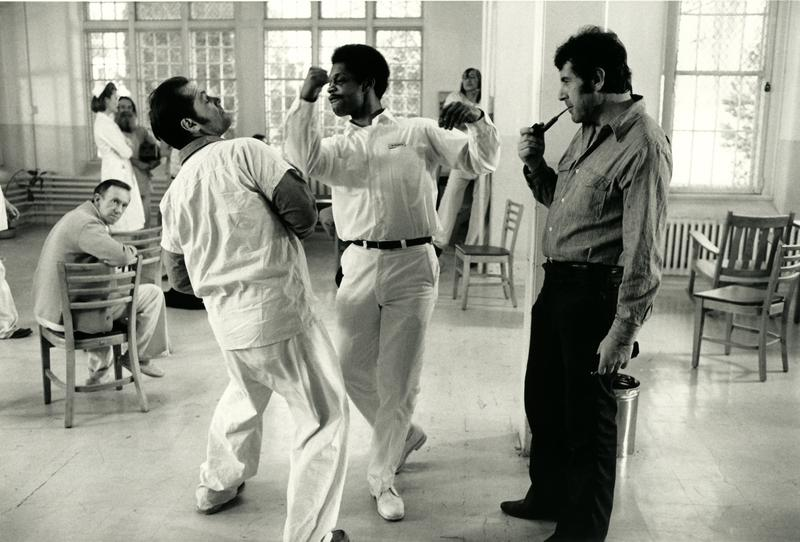 Jack Nicholson and another actor play a scene while director Milos Forman watches.