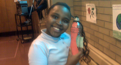 Katrina Freeman, age 9, at Earth Day party at P.S. 208 in Harlem with recyled water bottle art.
