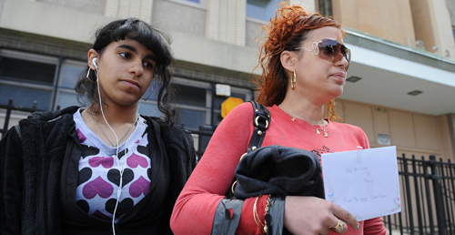Nancy Crespo and seventh-grade daughter Alexis Morales hold a get well card for assistant principal Mitch Wiener outside a closed Intermediate School 238 on May 15, 2009 (STAN HONDA/AFP/Getty Images)
