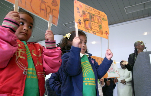 Children from the Audrey Johnson Day Care Center quietly protest city plans to close their school at hearing today.