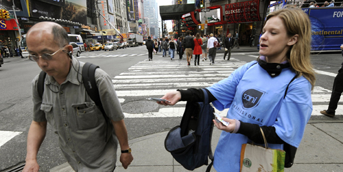 A woman hands out packages of hand sanitizing wipes at Times Square in New York on May 1, to help people take precautions against the spread of the swine flu in the city. (TIMOTHY A. CLARY/AFP/Getty Images)