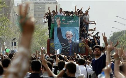 Monday's outpouring for Mousavi swelled as more people emerged from buildings and side streets wearing the trademark green of his campaign, following a decision by Iran's most powerful figure to investigate vote riggingallegations. (AP)
