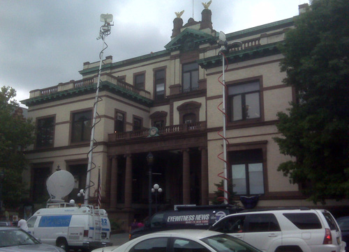 TV news trucks and reporters stake out Hoboken City Hall.