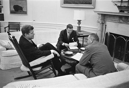 In March 16, 1961, JFK sits in his favorite rocking chair in his office during a meeting with Secretary of Defense Robert McNamara and Vice President Lyndon B. Johnson, right, at the White House.