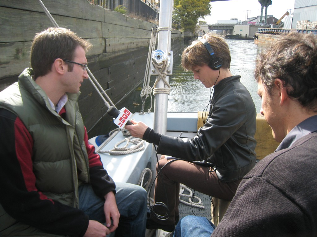 Amy Eddings interviews Riverkeeper staff attorney Josh Verleun (left) and Alex Matthiessen, executive director (right, foreground) on a boat in the Gowanus Canal.